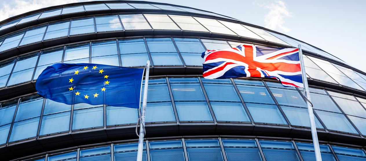 British and European Union flags in front of a building.